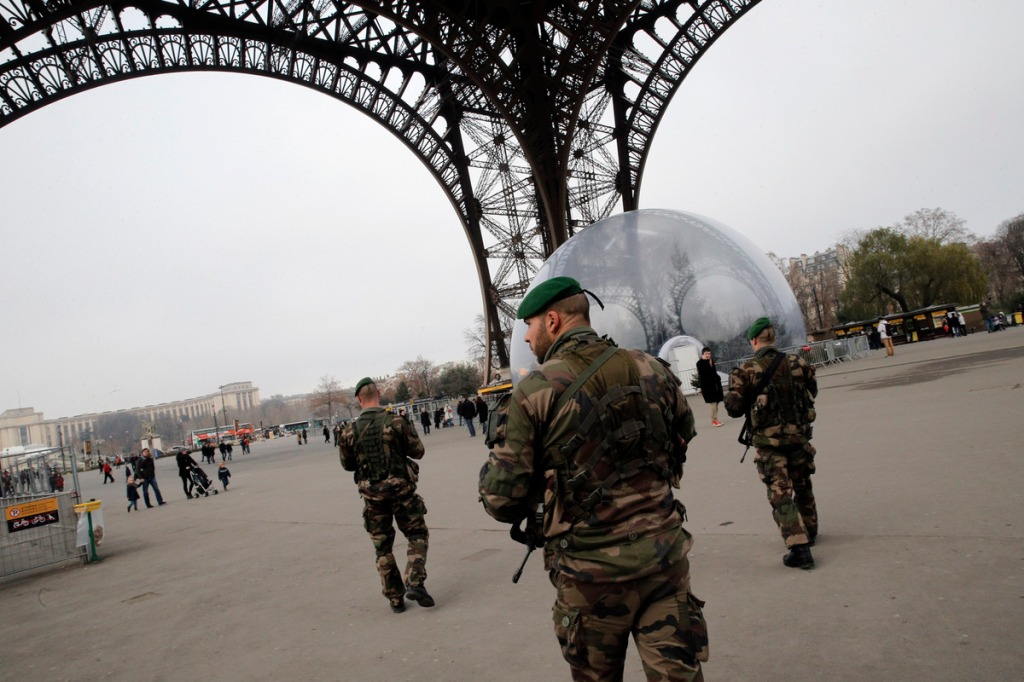 French soldiers patrols at the Eiffel Tower after a shooting at a French satirical newspaper, in Paris, France, Wednesday, Jan. 7, 2015. France reinforced security at houses of worship, stores, media offices and transportation after masked gunmen stormed the offices of a French satirical newspaper Wednesday, killing at least 11 people before escaping, police and a witness said. The weekly has previously drawn condemnation from Muslims. (AP Photo/Christophe Ena)
