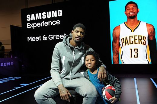 A basketball fan poses with Paul George at the Samsung Experience during NBA All-Star 2016