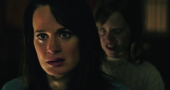 "(L to R) ALICE REASER is set upon by LULU WILSON as her daughter Doris in ""Ouija: Origin of Evil."" Inviting audiences again into the lore of the spirit board, the supernatural thriller tells a terrifying new tale as the follow-up to 2014's sleeper hit that opened at No. 1. In 1965 Los Angeles, a widowed mother and her two daughters add a new stunt to bolster their séance scam business and unwittingly invite authentic evil into their home. When the youngest daughter is overtaken by the merciless spirit, this small family confronts unthinkable fears to save her and send her possessor back to the other side."